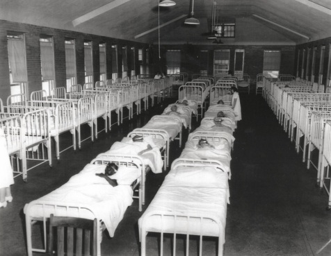 "Chicago Times, 1958. Inscription on back reads: ""Crowded female infirmary at Manteno. All crib-like beds are occupied. Faces are blocked out to prevent identification. Women standing are attendants"""